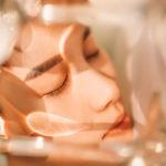 Frau mit geschlossenen Augen und Gesichtsserum auf dem Gesicht
