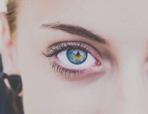Junge Frau schaut den Leser mit einem Auge an