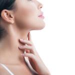 Junge Frau berührt ihren Hals nach Halsstraffung