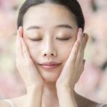 Junge Asiantin mit Glow auf der Haut nach Gesichtsöl