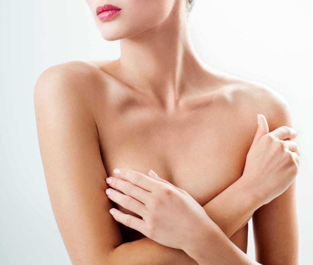 Junge Frau verdeckt ihre Brust